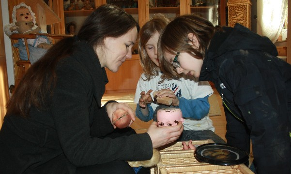 So sehen alte Puppen von innen aus? Sonja Voss weiht die Jungs in die Geheimnisse der Spielzeugherstellung ein. (Sonja shows Janis how old dolls look on the inside.)