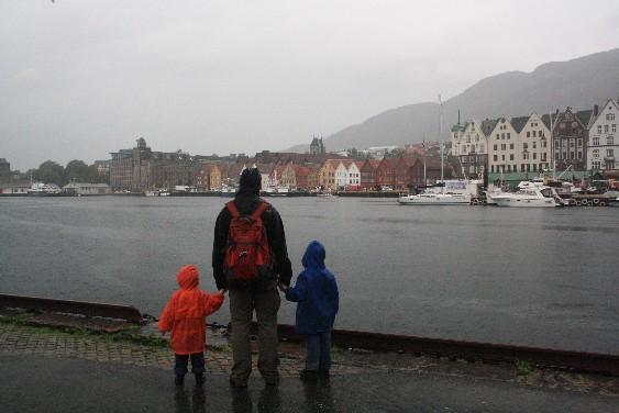 Typischer Anblick: Nasse Gestalten blicken über den Hafen auf die Brygge. (Typical view: wet people in front of Bergen's Brygge panorama.)
