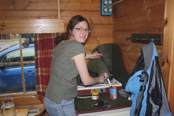 Spartanisch, aber effizient - zwei Kochplatten über dem Kühlschrank, ein Tisch, ein Schrank, zwei Doppelstockbetten, ein Spielplatz vor dem Fenster. Was braucht man mehr für eine Nacht?