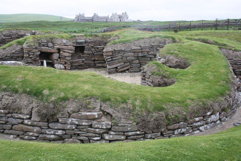 In der Jungsteinzeit war das Klima zwar etwas freundlicher zum Norden Schottlands, aber schon damals war es eine gute Idee, die Häuser halb in den Erdboden zu bauen und damit zu isolieren. Im Hintergrund ist Skraill House zu sehen, das ebenfalls besichtigt werden kann.