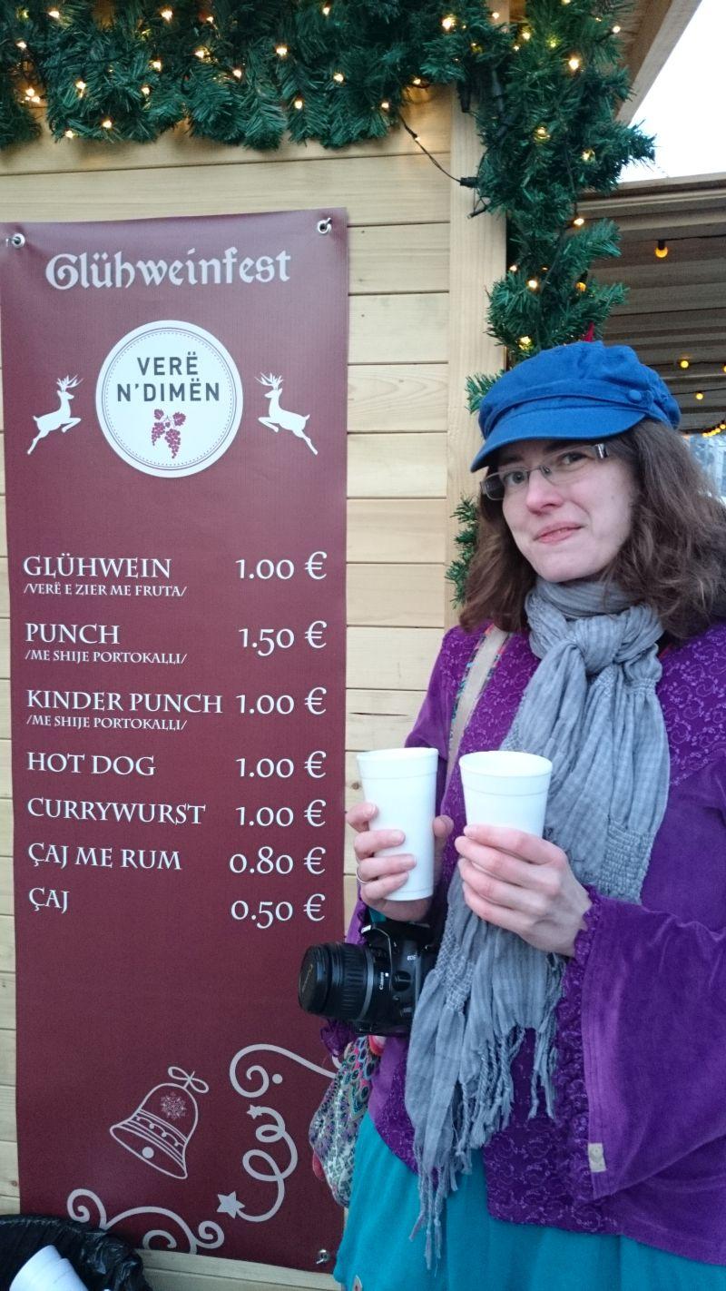 Lena mit Glühwein. Freiwillig (auch wenn der Gesichtsausdruck anderes nahelegt). Passiert so nur auf dem Weihnachtsmarkt im Kosovo.