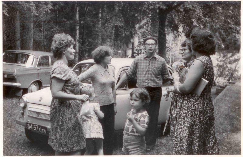 """Zu diesem Foto schreibt Reet: """"Auf dem alten Foto bin ich drei Jahre alt, mich sieht man aber nicht so gut. Der familieneigene """"Moskwich"""" steht ganz hinten. Wir sind da beim Sommerhaus von meinem Urgrossonkel (der hatte sein Haus an mehrere Verwandte vererbt, also trafen sich viele Familien dort). Es wurde zusammen gekocht, Ausflüge gemacht und in die Sauna gegangen. Noch heute fahren mehrere Cousins mit ihren Familien hin, wir aber lange nicht mehr. Es liegt ca 25 km südlich von Tartu und dorthin habe ich meine ersten """"Reisen"""" gemacht."""""""
